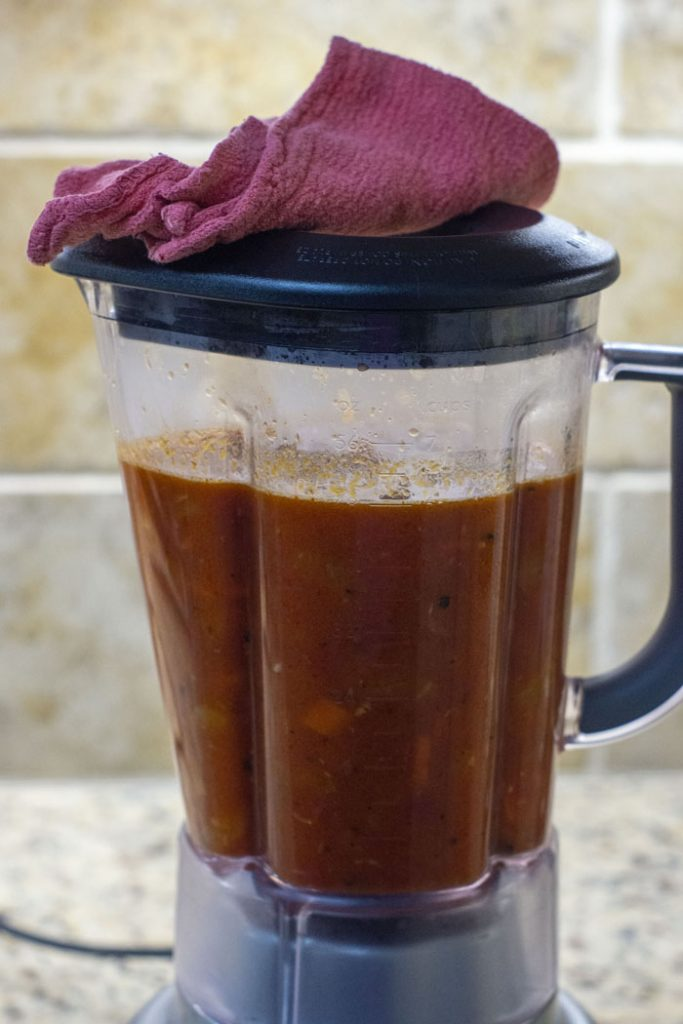 Tomato soup in a blender covered with a rag