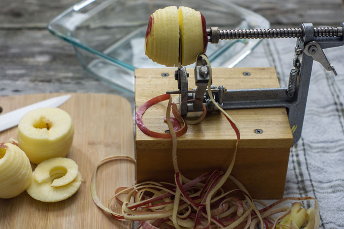 Apple corer and slicer with an apple halfway through the machine sitting on a white and grey towel next to a wooden cutting board with a few sliced apples on it with a glass baking dish in the background all on a wooden surface