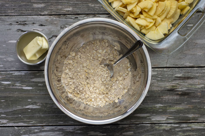 Large stainless steel mixing bowl with oats, flour, brown sugar, and cinnamon mixed together with a spoon in the bowl sitting next to another stainless steel bowl with softened butter and a glass dish with sliced apples behind all on a wooden surface