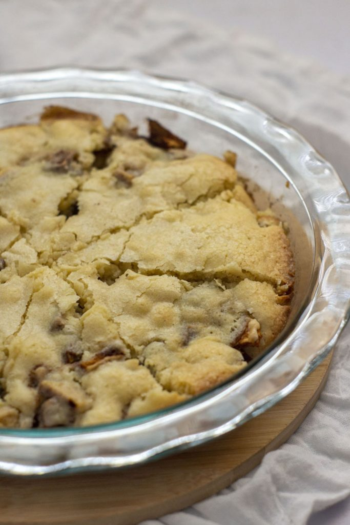 Baked easy apple pie in a glass pie pan on a circular bamboo platter on a white cloth surface (vertical)
