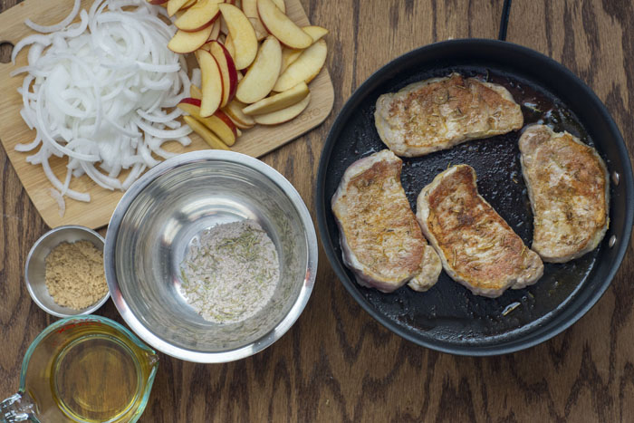 Skillet with cooked pork chops next to a stainless steel bowl of an herb mixture and another stainless steel bowl with brown sugar, a glass measuring cup with apple sauce, and a bamboo cutting board with sliced apples and onions all on a wooden surface