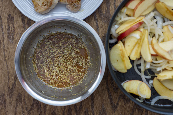 Close up of a stainless steel bowl with an herb mixture with apple juice next to a skillet of cooked sliced onions and apples and the edge of a white plate with cooked pork chops above all on a wooden surface