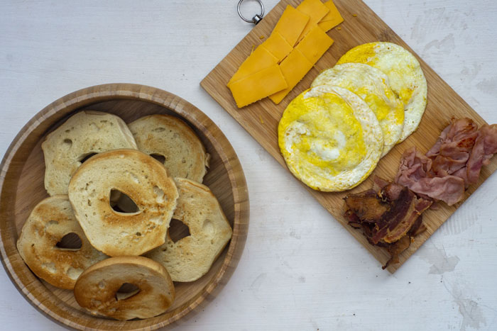 Bamboo bowl of toasted bagel slices next to a wooden cutting board with slices of cheese, cooked eggs, and cooked bacon and ham on a white and grey surface