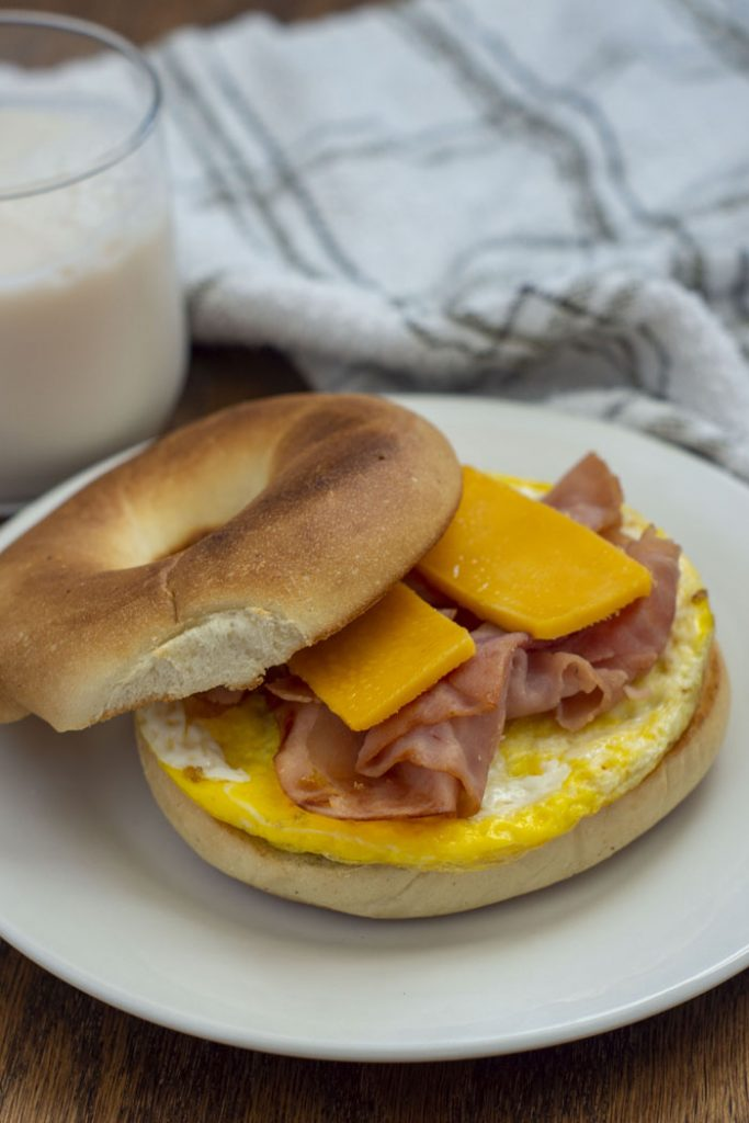Breakfast bagel with egg, ham, and sliced cheese on a round white plate next to a glass of milk and a grey and white towel on a wooden surface (vertical)