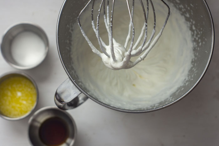 Stainless steel mixing bowl for stand mixer filled with whipped heavy cream next to three small stainless steel bowls with melted butter, sugar, and vanilla extract all on a white surface