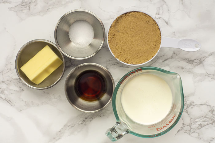 Butterscotch syrup ingredients ready: stainless steel bowls with stick butter, salt, vanilla extract, a glass measuring cup with heavy cream, and a measuring cup with brown sugar on a white and grey marble surface