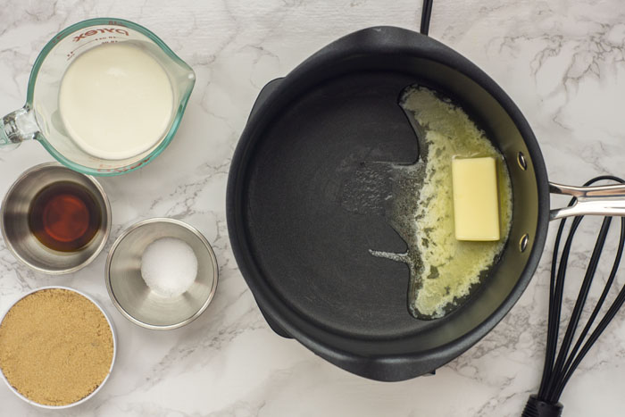 Medium saucepan with melting butter next to a nylon whisk, stainless steel bowls with salt and vanilla extract, a measuring cup of brown sugar and a glass measuring cup of heavy whipping cream all on a grey and white marble surface