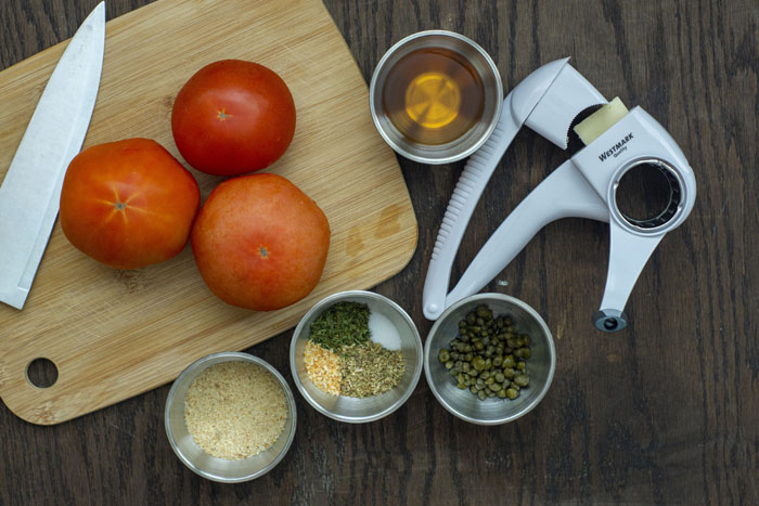 Bamboo cutting board with three tomatoes and a chef's knife on top next to stainless steel bowls with bread crumbs, herbs, capers, and cooking sherry with a cheese grater to the side all on a wooden surface