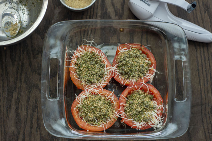 Glass baking dish with tomatoes filled with shredded cheese and herb-caper mixture next to a stainless steel bowl with the remnants of herb mixture inside, another stainless steel bowl with bread crumbs, and a cheese grater all on a wooden surface