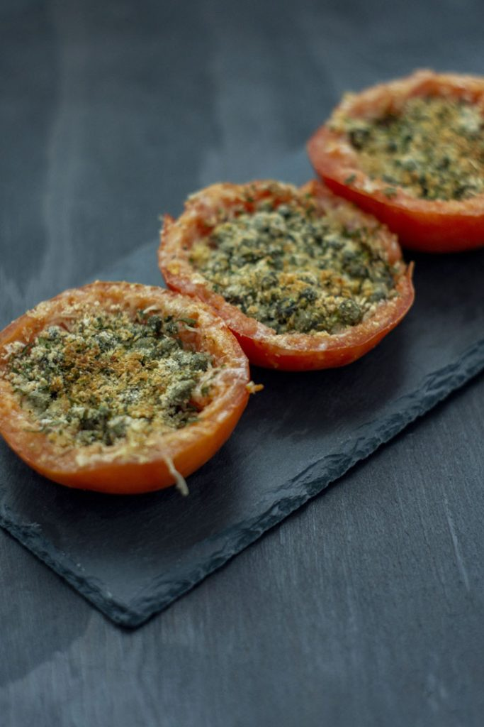 Three Cheesy Caper-Stuffed Tomatoes on a slate serving dish on a dark wooden surface (vertical)