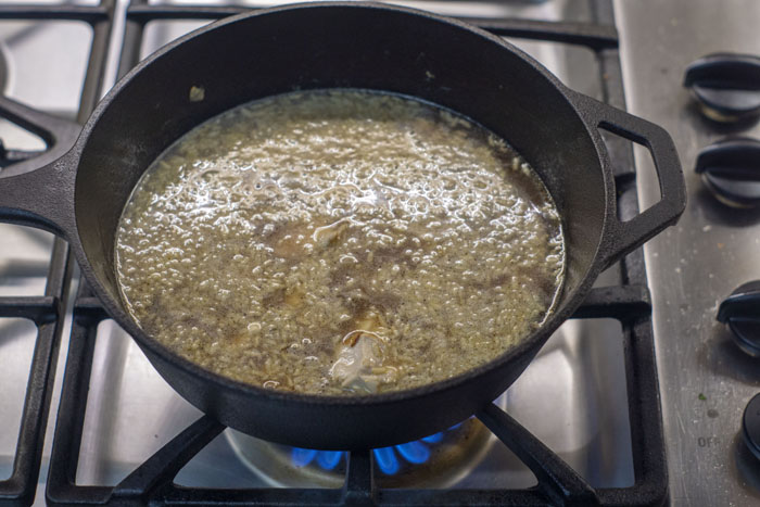 Large cast-iron pan with onion, chicken, rice, and broth over a gas stovetop