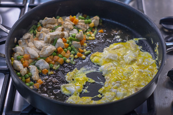 Large skillet with bite-sized chicken and frozen vegetables in a pan next to eggs scrambling on a gas stovetop