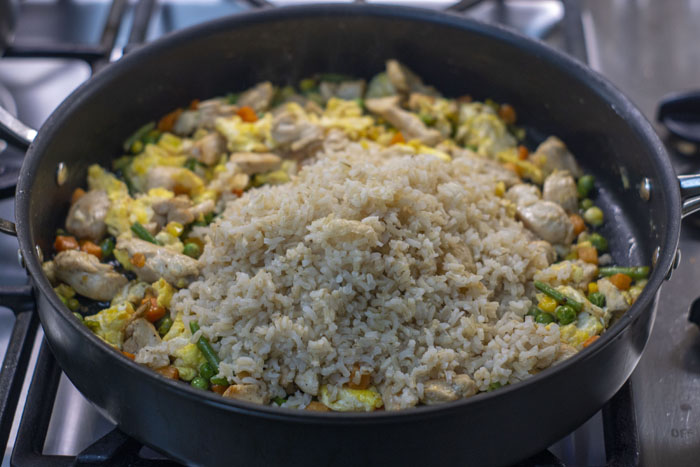 Large skillet with bite-sized chicken, vegetables, and scrambled eggs covered with a pile of cooked brown rice over a gas stovetop