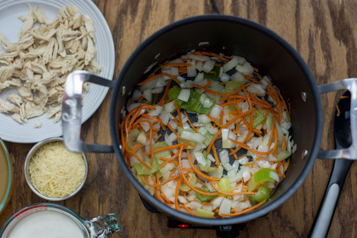 Large stockpot with onion, celery, carrots, and garlic cooking in oil next to a white plate with shredded chicken a glass measuring cup of heavy whipping cream, a stainless steel bowl of shredded cheese, and a stirring spoon all on a wooden surface