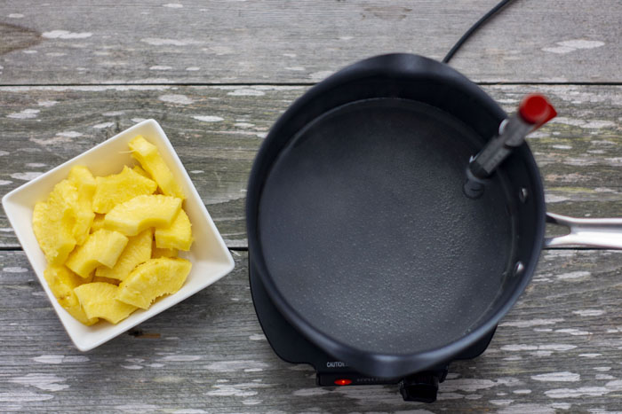 Medium saucepan with sugar and water simmering with a candy thermometer on the side of the pan next to a square white bowl of sliced pineapple all on a wooden surface