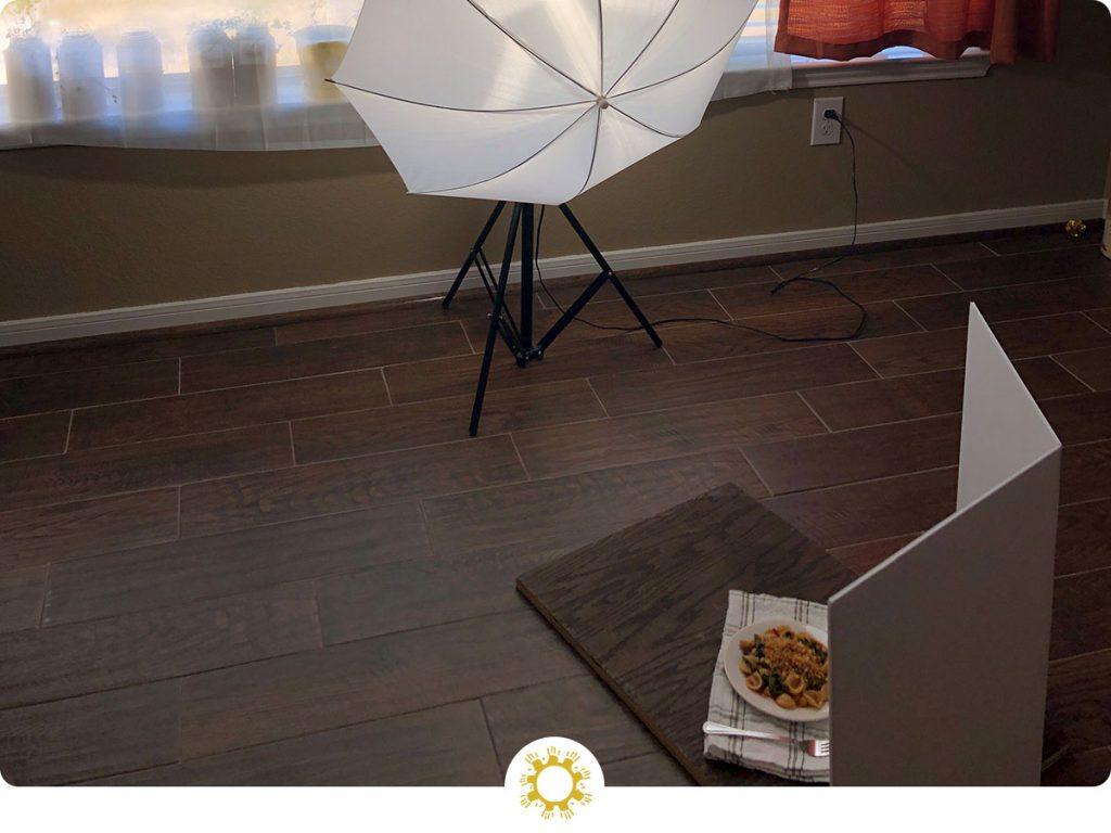 Behind the scenes of food on a white plate with a towel and fork on a small wooden board with a white foam board reflector behind it and an umbrella light in front (with logo overlay)