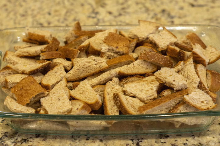 Large glass baking dish filled with chunks of bread sitting on a granite countertop