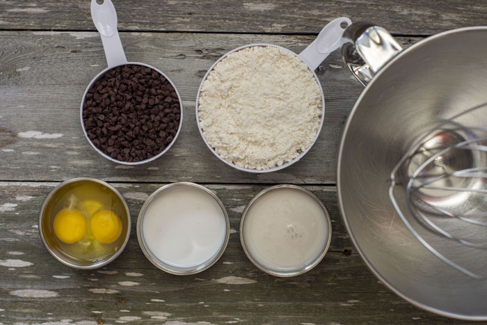 Stainless steel bowls with eggs, milk, and creamer below plastic measuring cups of mini chocolate chips and bisquick next to a stand mixer all on a wooden surface