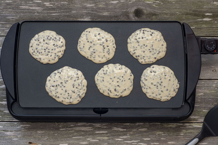 Six small pancakes on a large flat skillet on a wooden surface