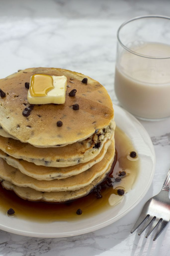 Stack of five chocolate chip pancakes topped with a pat of butter and syrup on a round white plate next to a stainless steel fork and a glass of milk all on a white and grey marble surface (vertical)