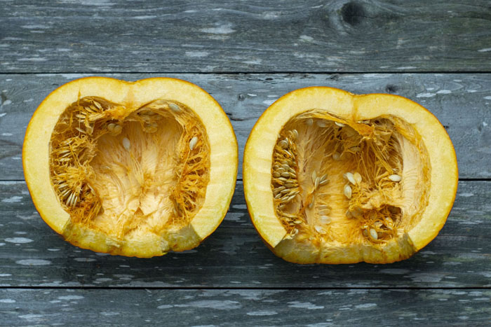 Pumpkin cut in half laying on a wooden surface