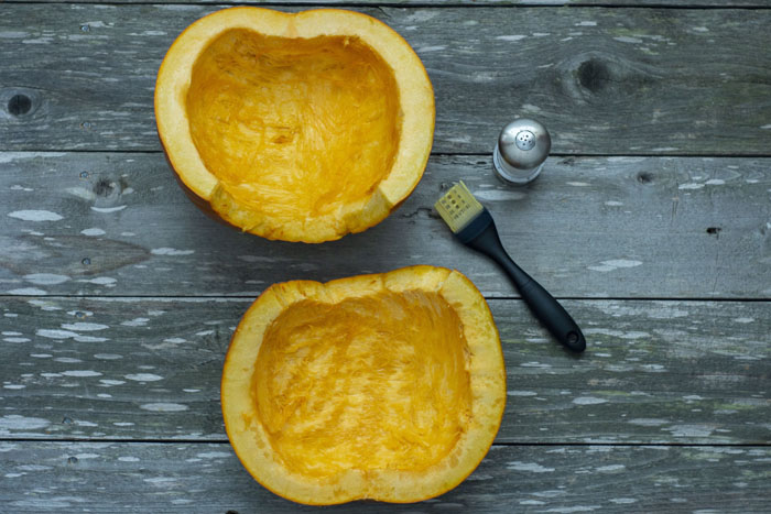 Two halves of a pumpkin brushed with oil and sprinkled with salt next to a pastry brush and salt shaker laying on a wooden surface