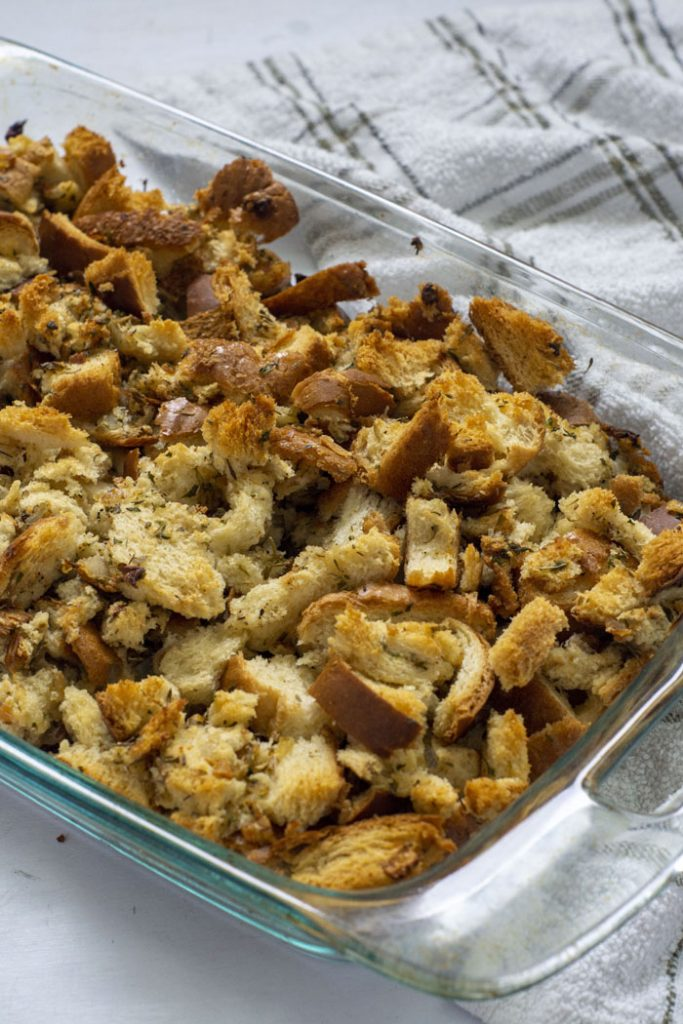 Baked homemade stuffing in a glass baking dish on top of a white and brown towel all on a white surface (vertical)
