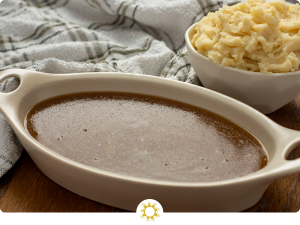 Homemade brown gravy in an oval white dish next to a white bowl of mashed potatoes with a white and green towel behind all on a wooden surface (with logo overlay)