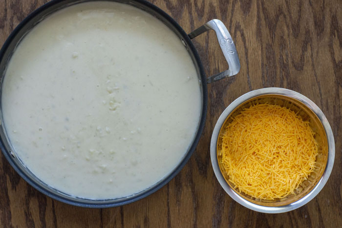 Large skillet with cream mixture next to a stainless steel bowl of shredded cheddar cheese on a brown wooden surface