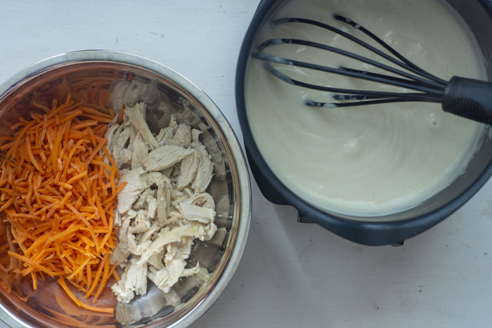 Medium saucepan filled with gravy and a nylon whisk next to a stainless steel mixing bowl of shredded chicken and shredded carrots all on a white surface