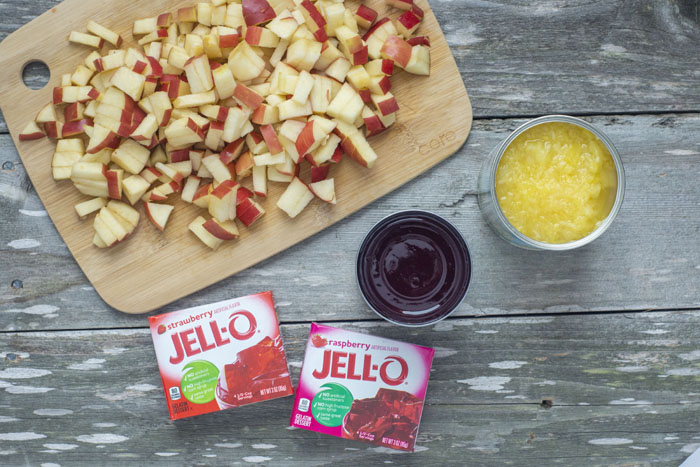 Diced apples on a bamboo board next to a can of crushed pineapple, a can of cranberry sauce, and two boxes of jello all on a wooden surface