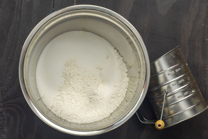 Stainless steel bowl of flour and sugar next to a metal sifter on a wooden surface