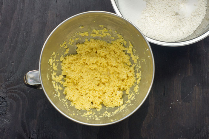 Mixing bowl with egg yolk mixture next to a stainless steel bowl with flour on a wooden surface