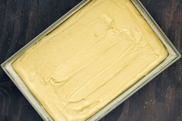 Cake batter in a metal cake pan on a wooden surface