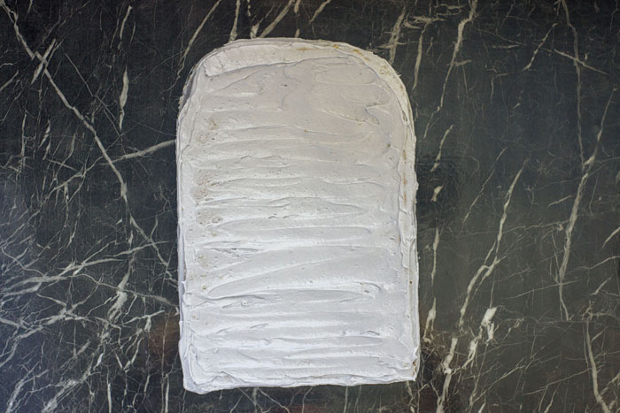 Rectangular cake with top corners rounded covered in light gray frosting on a dark granite surface