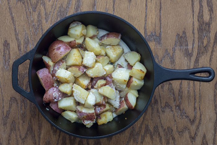 Cast-iron pan with diced potatoes covered with milk on a wooden surface