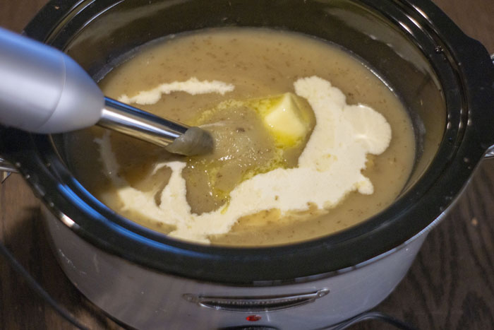 Immersion blender mixing butter, cheddar cheese, and cream into cooked potato and broth mixture