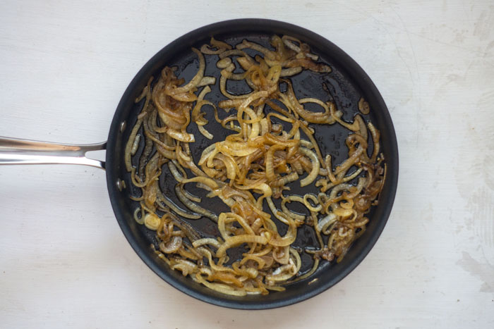 Skillet with cooked onions on a white surface