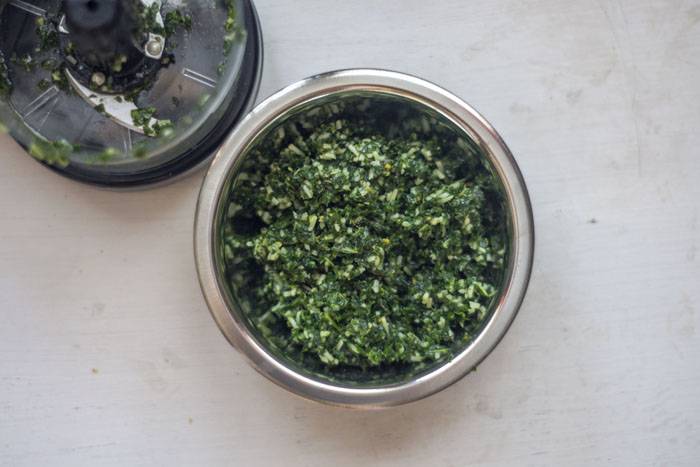 Stainless steel bowl of kale pesto next to a food processor on a white surface