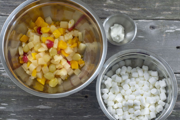Large stainless steel bowl with drained fruit cocktail next to a medium stainless steel bowl with mini marshmallows and a small stainless steel bowl with sour cream all on a wooden surface