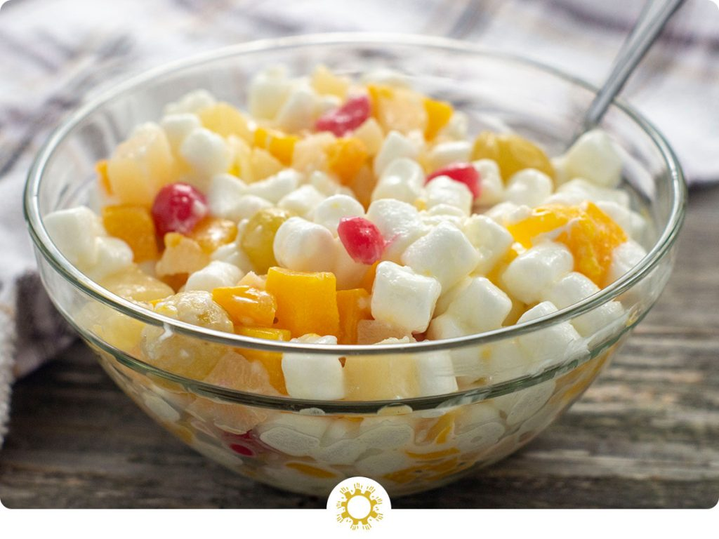 Ambrosia salad in a clear glass bowl in front of a white and brown towel all on a wooden surface (with logo overlay)