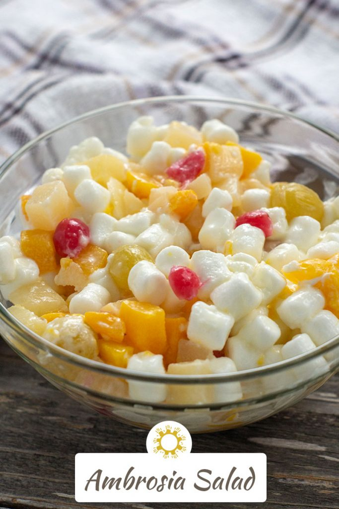 Ambrosia salad in a clear glass bowl in front of a white and brown towel all on a wooden surface (vertical with title overlay)