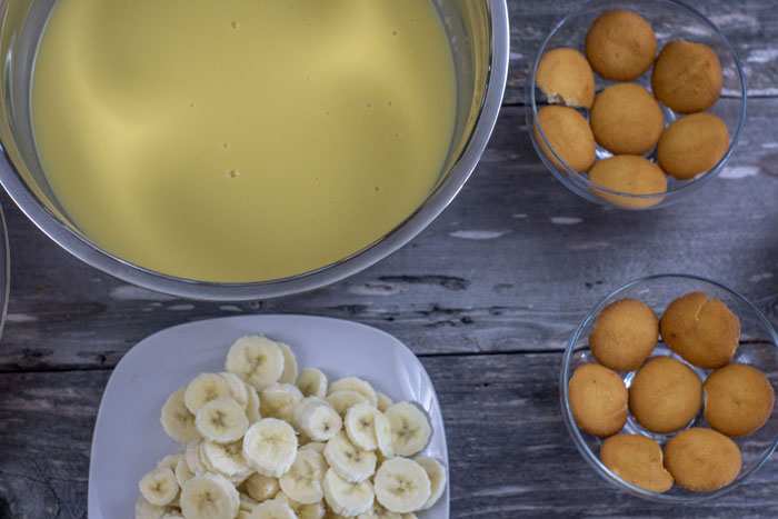 Stainless steel bowl with pudding mixture next to a plate of sliced bananas and two individual dessert dishes with a layer of nilla wafers in each all on a wooden surface