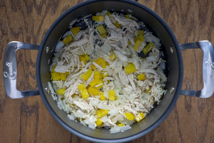 Sauteed vegetables with shredded chicken in a large stockpot on a wooden surface