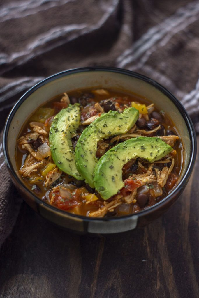 Chicken tortilla soup topped with sliced avocado and parsley in a brown bowl with a brown towel behind on a wooden surface (vertical)