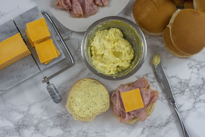 Marble cheese slicer with sharp cheddar cheese, white plate with slices of ham, and hamburger buns behind a stainless steel bowl with mixed butter, mustard, minced onion, and poppy seeds. Once bun is open with the butter mixture spread on both halves then topped with ham and a slice of cheese next to a knife all on a white and grey marble surface.