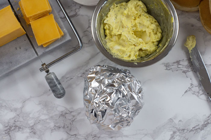 Christmas Sandwich wrapped in foil with a stainless steel bowl of butter mixture and a butter knife with mixture on it behind next to hamburger buns and a marble cheese slicer with cheddar cheese all on a white and grey marble surface
