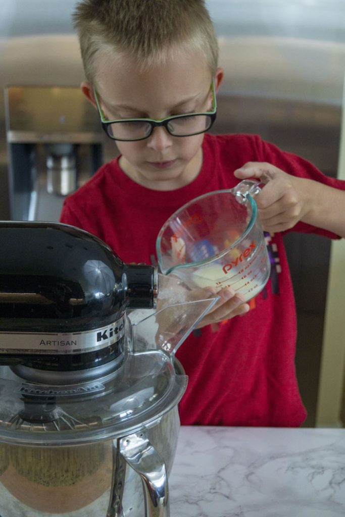 Young boy pouring liquid ingredients into a stand mixer