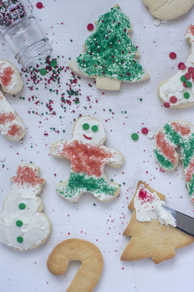 Christmas sugar cookies on a white surface with some frosted and decorated and a few unfrosted with spilled sprinkles (vertical)
