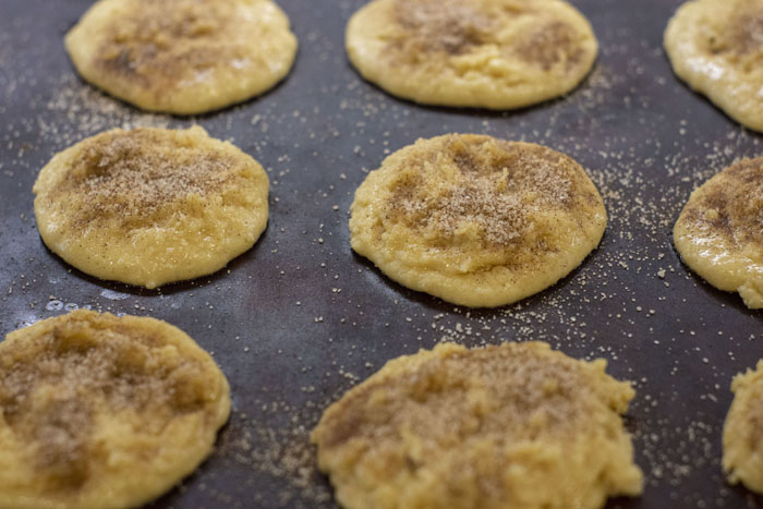 Baking stone with scoops of cookie dough sprinkled with cinnamon sugar mixture